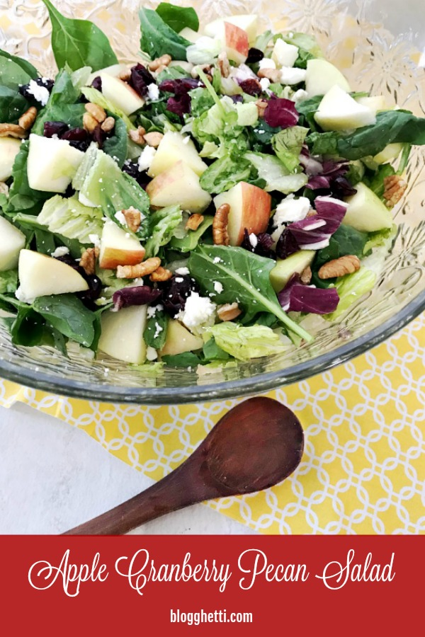 Apple Cranberry Pecan Salad in crystal bowl with a small wooden spoon - pin image