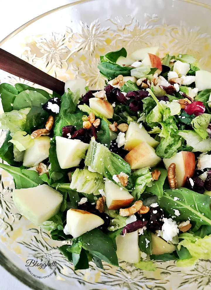Crystal salad bowl filled with apple cranberry pecan and spinach salad