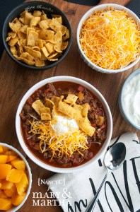 bowl of sweet and sassy chili with bowls of chili toppings like cheese, peaches and more