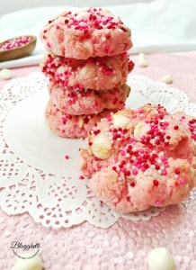 strawberry cheesecake cookies with white chocolate stacked on a white doily