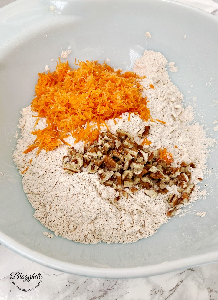 adding ingredients for carrot cake scones in bowl