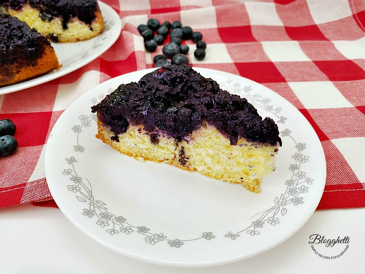 a slice of blueberry upside down cake on white plate with red checkered towel