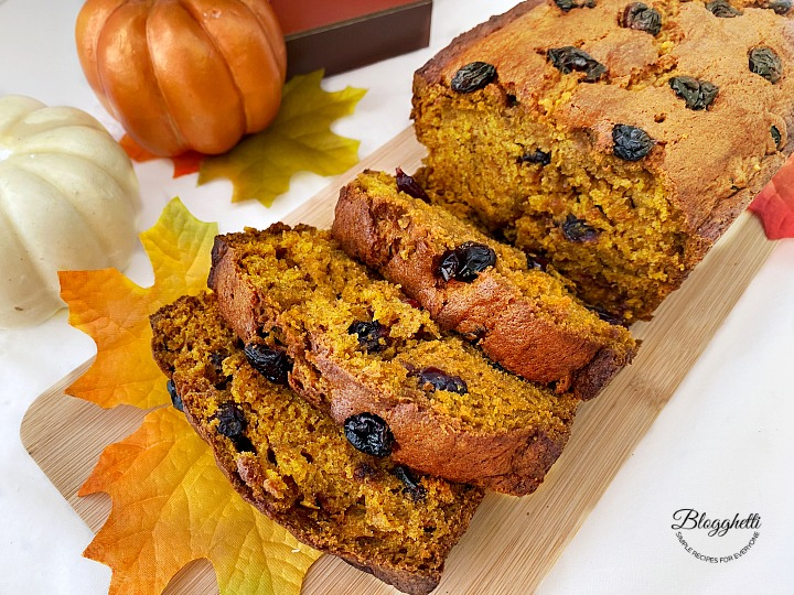 Slices of pumpkin cranberry bread on wooden board with fall decor