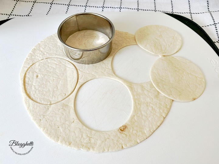 cutting flour tortilla shells into 4 inch circles