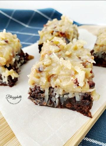 square bites of German chocolate brownies on wooden board
