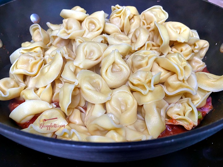 adding the tortellini to the skillet with Tuscan sauce
