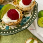 close up of key lime mini tarts with raspberry garnish