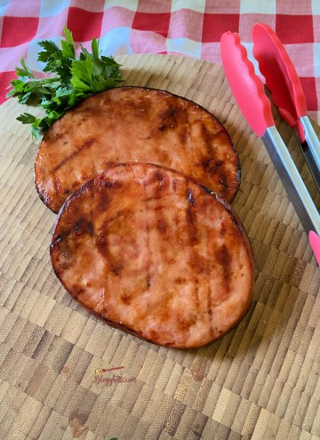 Grilled ham steaks with homemade honey mustard glaze on cutting board