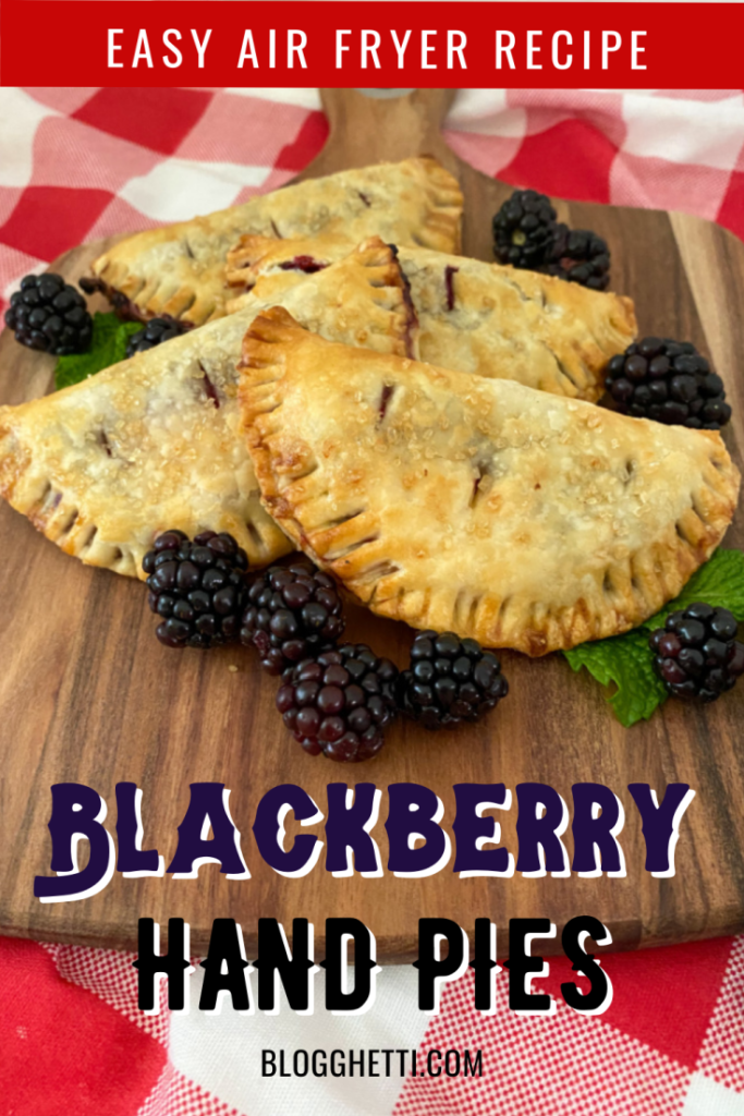 air fried blackberry hand pies on wooden tray with fresh blackberries and mint leaves for garnish