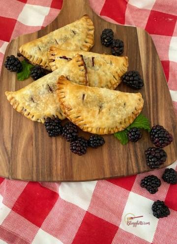 mini blackberry hand pies on wooden board