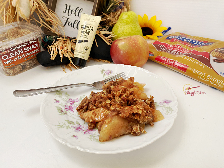serving of apple pear crisp on white plate with some of the ingredients in the background