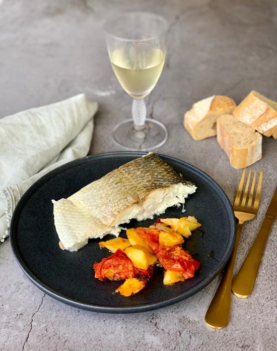 lomo de lubina Aquanaria al horno, junto con pan y una copa de vino blanco. Lubina Aquanaria en casa