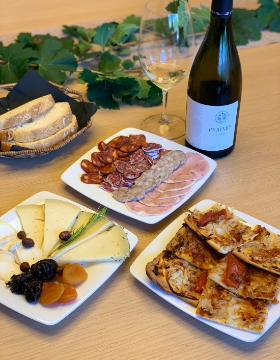 botella de vino de Perinet, coca de recapte, quesos, embutidos
