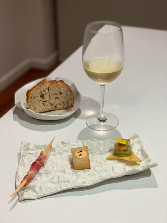 copa de vino, pan, jamón, patata brava y nacho con guacamole
