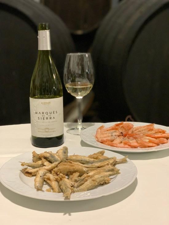 Boquerones fritos sobre un plato acompañado de una copa y una botella de vino Marqués de la Sierra