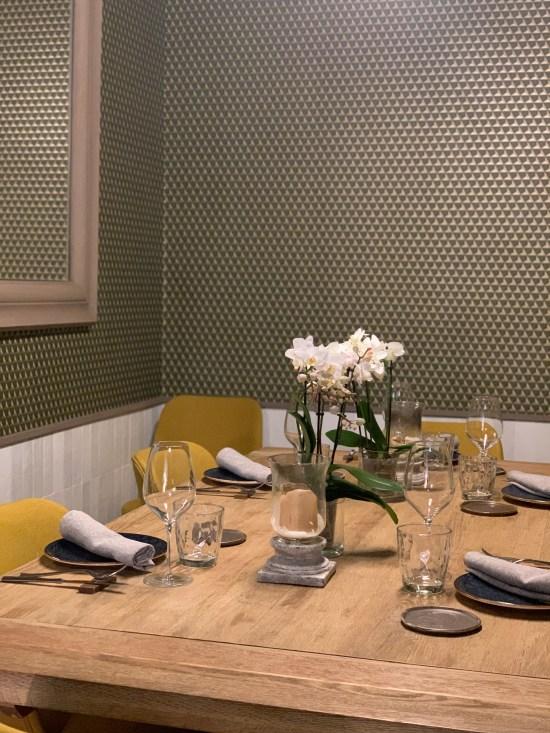mesa de madera, cubiertos, vajilla y cristalería. flores