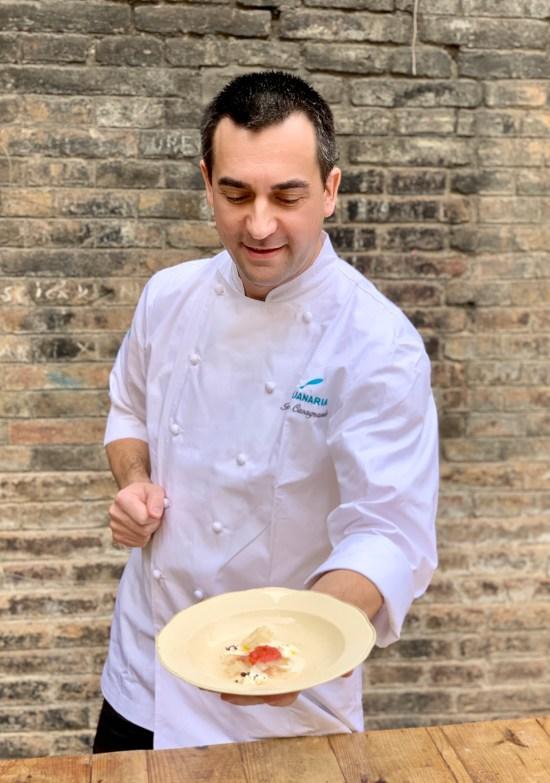 chef presentanto un plato con lubina ahumada