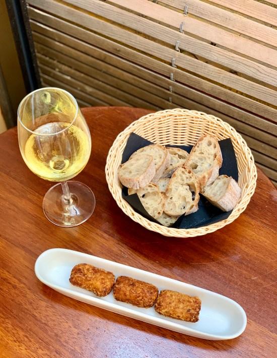 croquetas, pan y copa de vino blanco en Tejada Mar del chef Romain Fornell