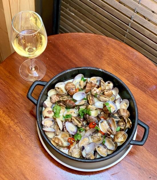 almejas y copa de vino. En Tejada Mar del chef Romain Fornell