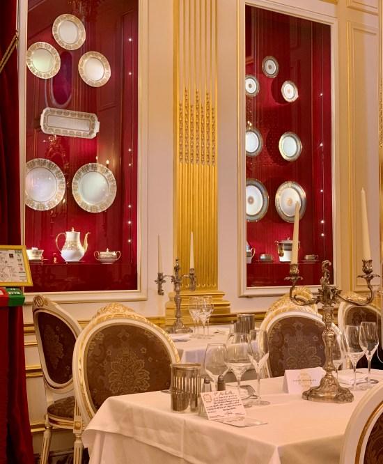 vitrina con porcelana, y mesas preparadas para recibir a los clientes. En Le Salon Doré de Les Grands Buffets