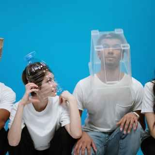 Neljä ihmistä joilla on erilaisia hengityssuojaimia