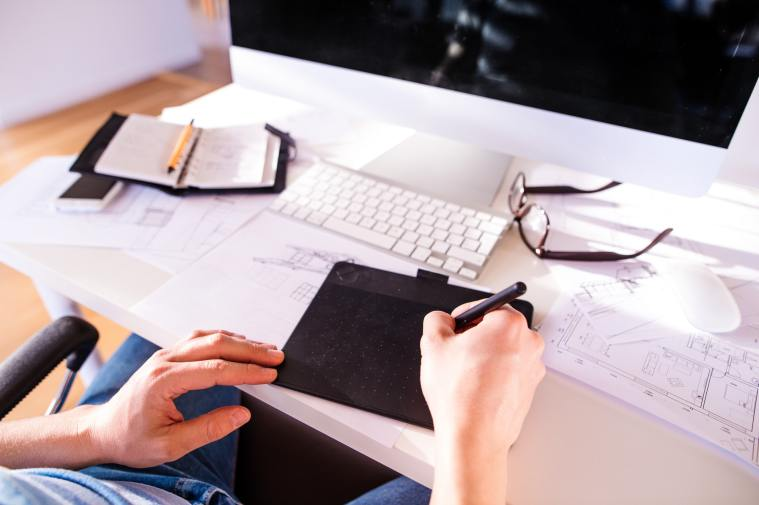 Unrecognizable man working from home writing on graphic tablet