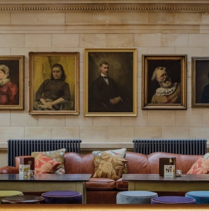 COSY CLUB INTERIOR COUCH AND PORTRAIT ART IN FRAMES