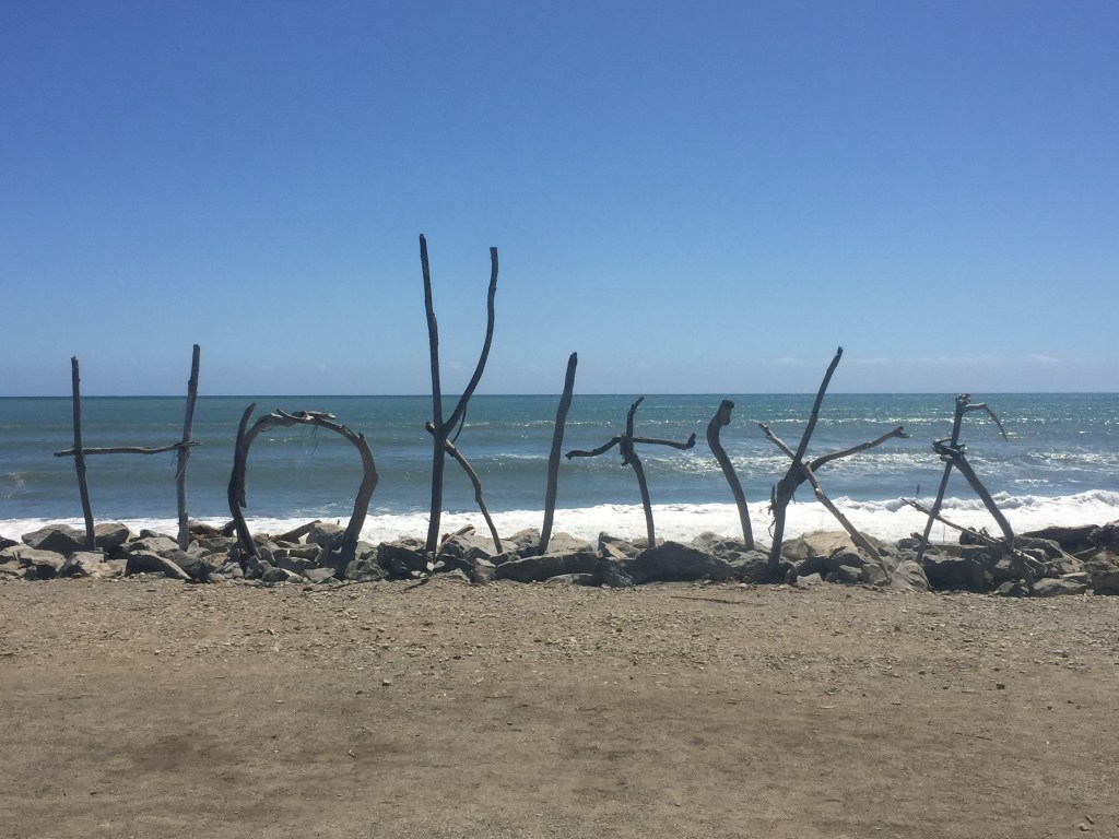 hokitika driftwood sign on beach