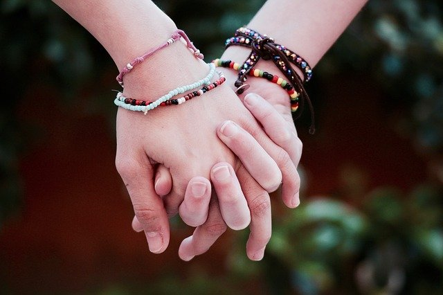 beaded bracelets old wrists holding hands