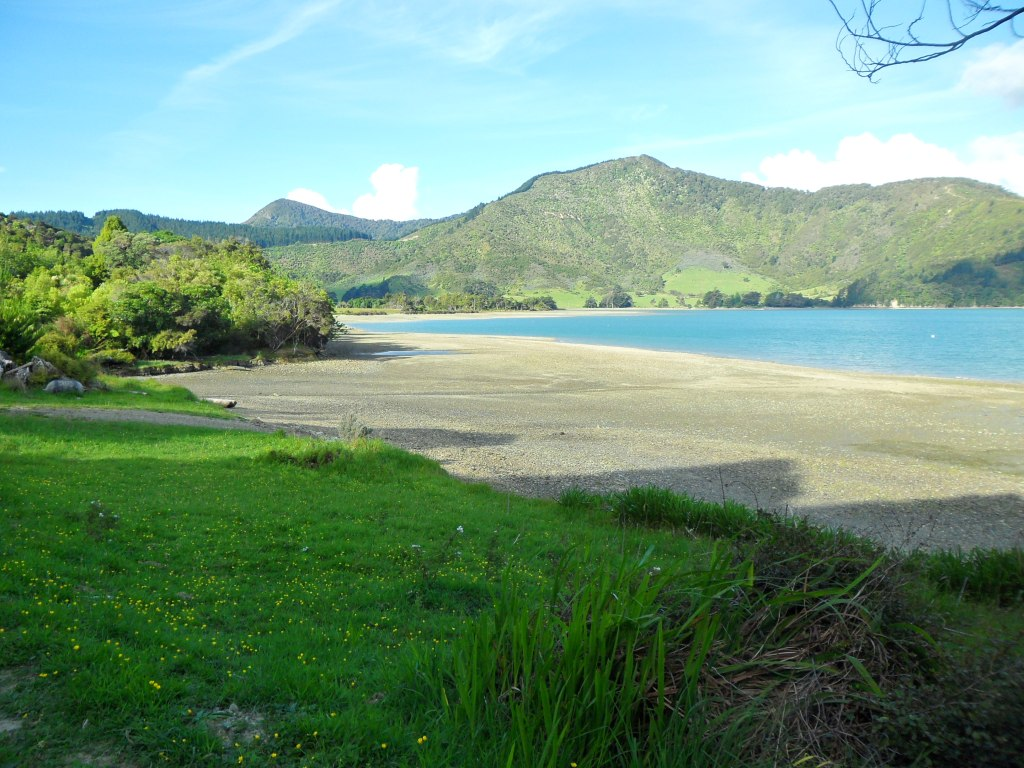 Sun and shade on the beach with green hills