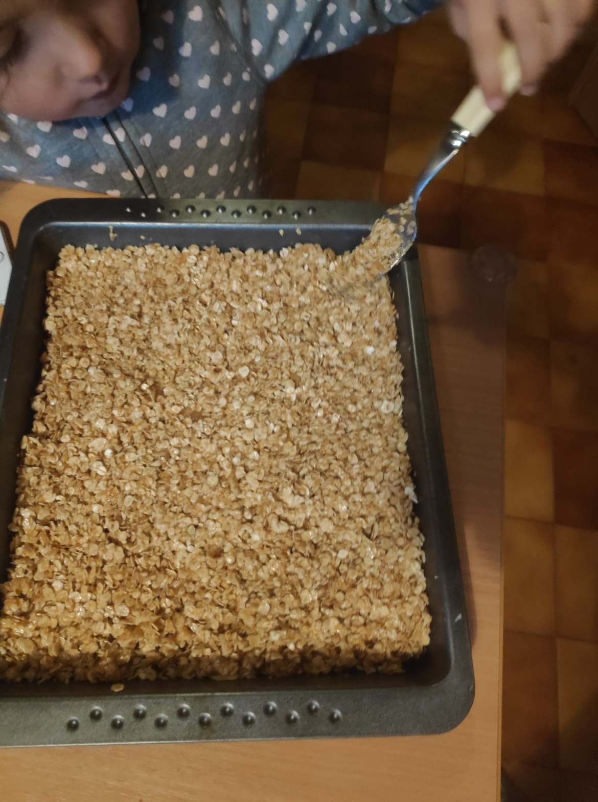 Tray of flapjacks getting flattened with a fork by a child