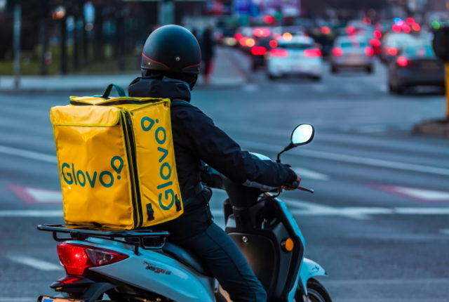 Glovo e DIA fazem aliança na Espanha foto: Bucharest, Romania - January 28, 2020: A Glovo food delivery courier delivers food in Bucharest, Romania