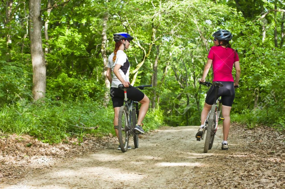 20615862-two-girls-riding-the-bicycle-in-the-forest-Stock-Photo