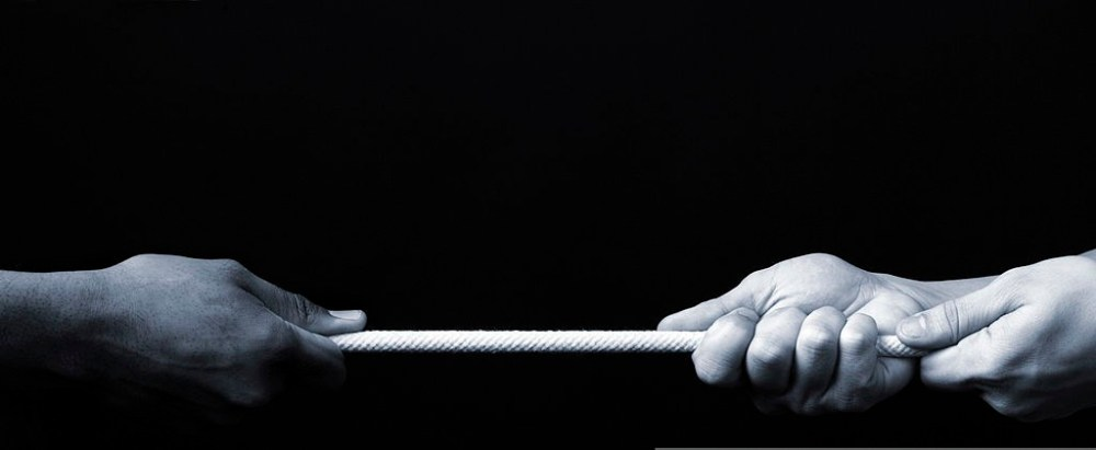 Two white hands and one black hand pulling the same rope.