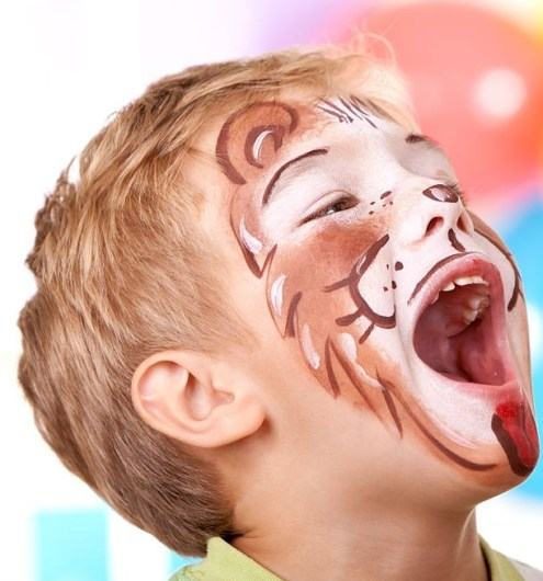 Happy little boy with lion face paint, enjoying birthday party.