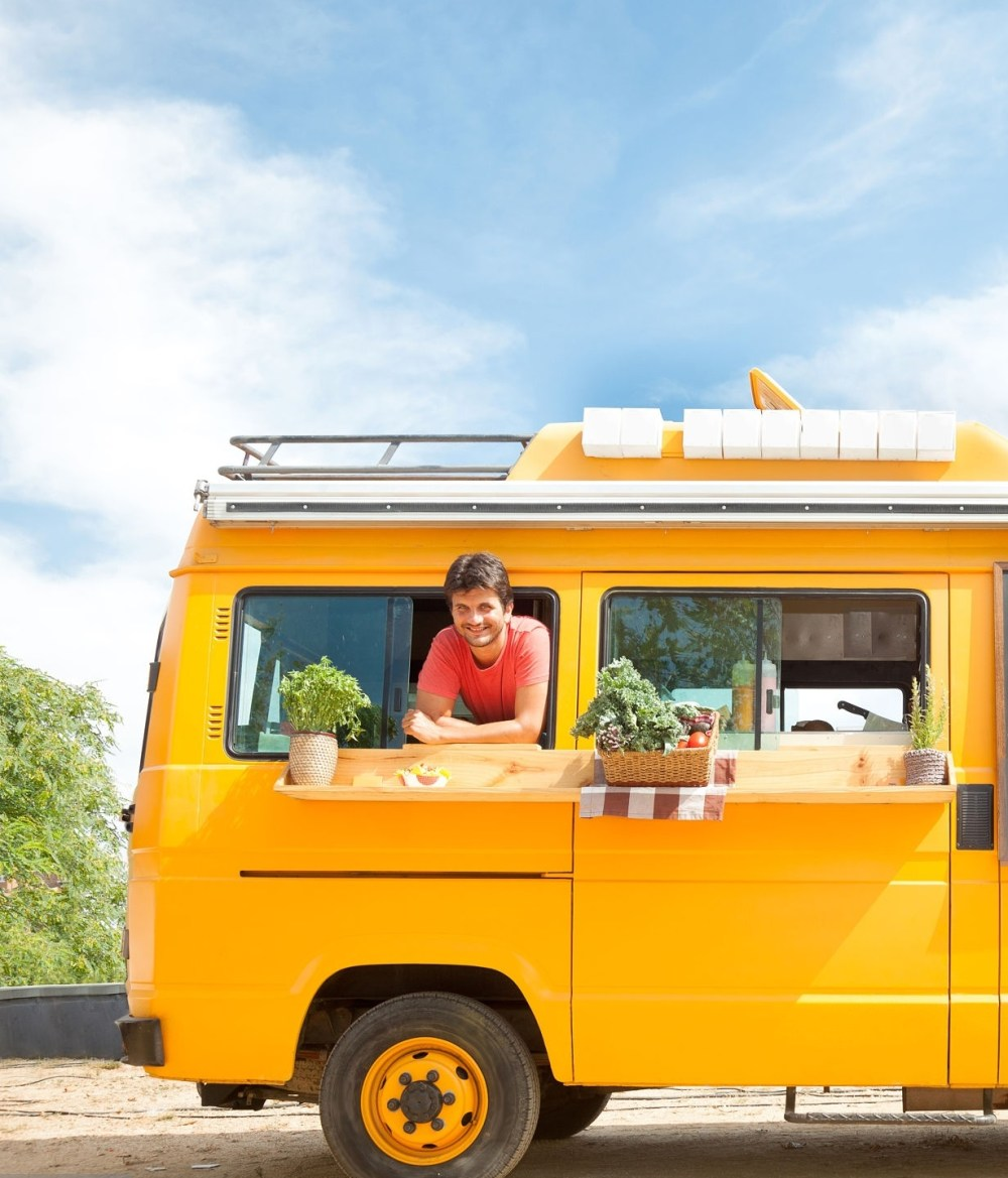 Yellow food truck open and parked in the street, with owner.