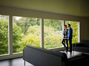Husband and wife standing near window in living room of contemporary home laughing