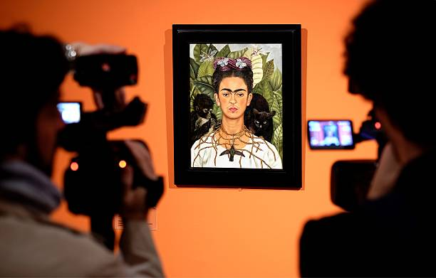 """Cameramen film the """"Self-portrait with with Thorn Necklace and Hummingbird"""" by Mexican artist Frida Kahlo during an exhibition in Rome's Scuderie del Quirinale on March 18, 2014. The Scuderie del Quirinale host a exhibition on the life and work of Mexican artist Frida Kahlo (1907-1954), a symbol of the artistic avant-garde and exuberance of Mexican culture in the 20th century. The exhibition will run from March 20 until August 31, 2014. AFP PHOTO / ALBERTO PIZZOLI RESTRICTED TO EDITORIAL USE, MANDATORY CREDIT OF THE ARTIST, TO ILLUSTRATE THE EVENT AS SPECIFIED IN THE CAPTION (Photo credit should read ALBERTO PIZZOLI/AFP via Getty Images)"""