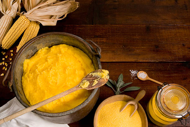 Polenta with corn flour and corn cobs on a wooden background
