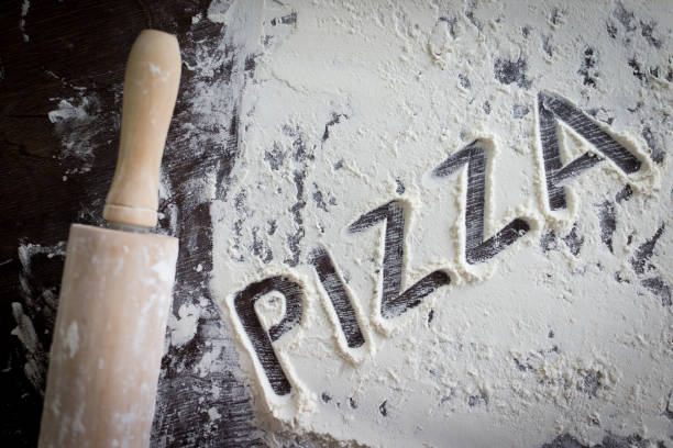 Flour for dough with rolling pin on table in kitchen