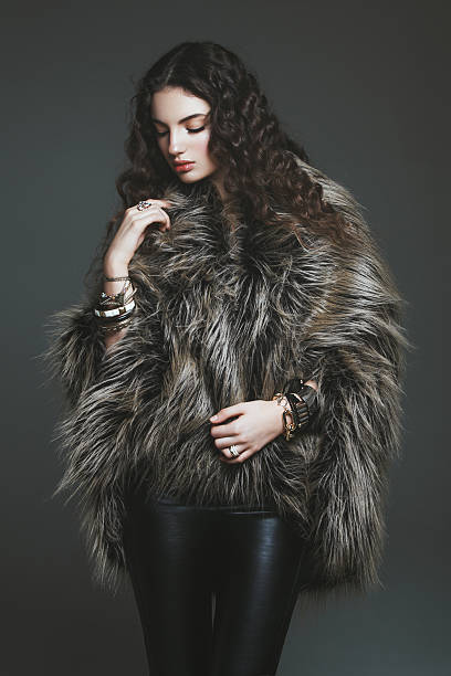 Young fashionable woman wearing faux fur coat and leather pants. Professional make-up and hairstyle.
