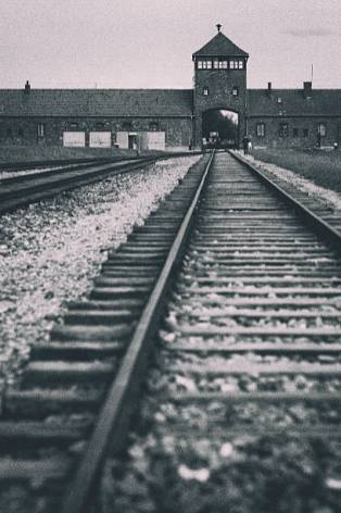 Oswiecim, Poland - August 16, 2016: Train tracks inside the former concentration camp Auschwitz II, also known as Birkenau, leading up to the main gate of the camp.