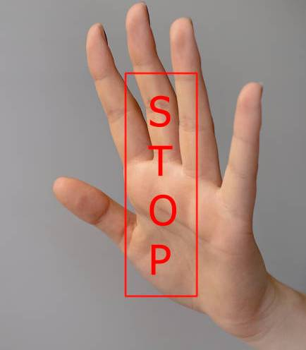 One female hand makes a stop sign with the word 'STOP' added.