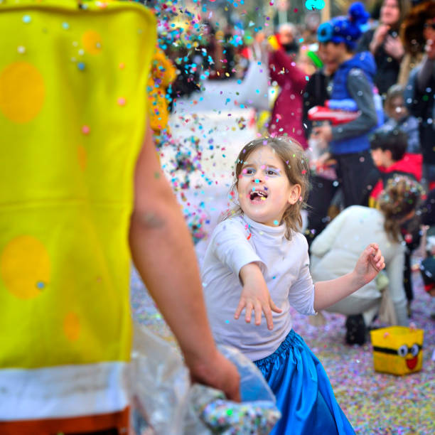 Sion, Switzerland - February 6, 2016: The little girl Tossed confetti in the carnival parade. Sion's carnival, Switzerland.