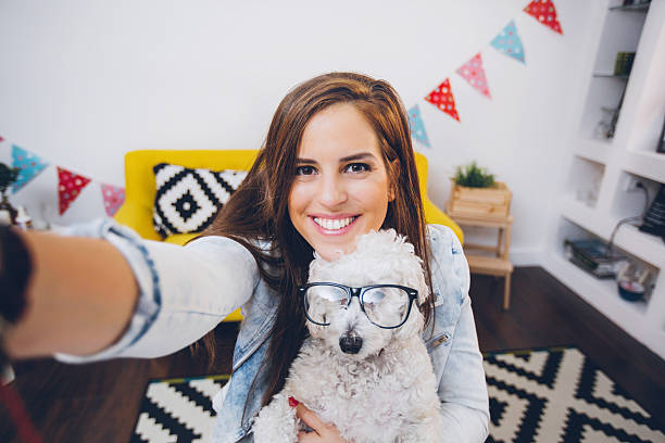 Woman in her modern home office holding cute white dog and making selfie