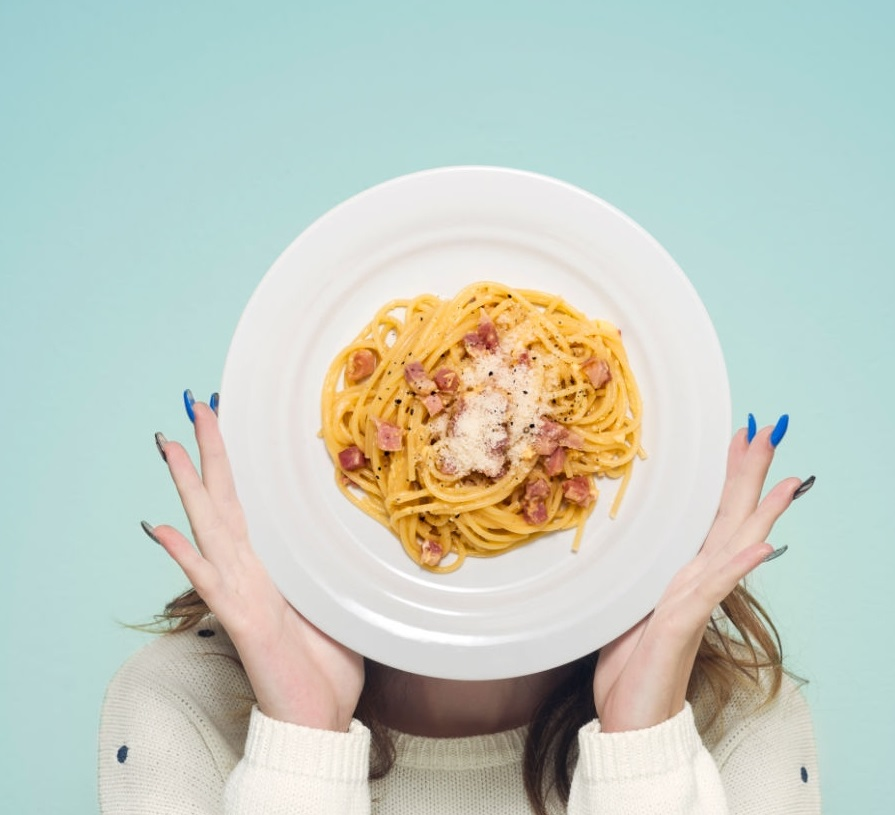 Woman hiding face with carbonara spaghetti plate