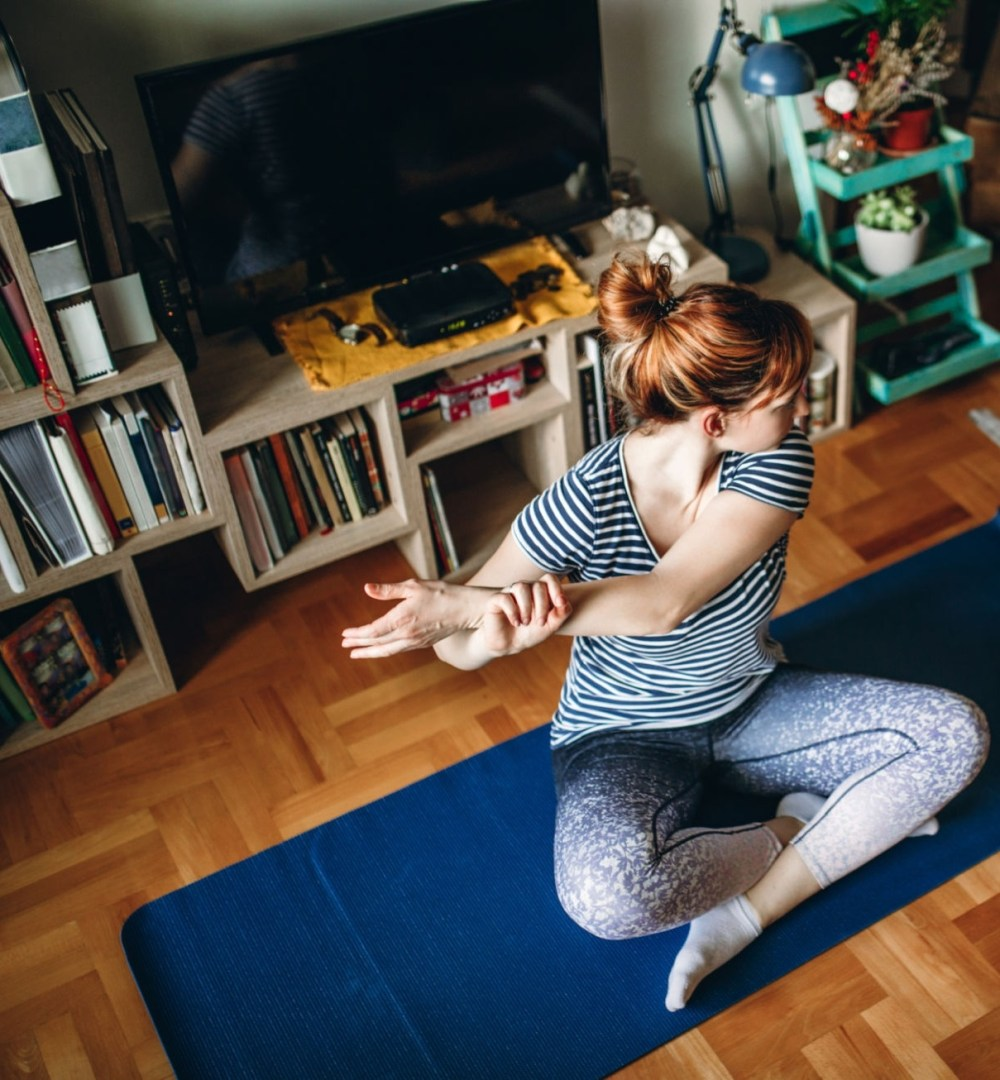 Young woman practicing yoga and stretching her body alone in the living room
