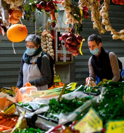 People wearing a respiratory mask shop for fruits and vegetable at the Trionfale Market (Mercato Trionfale) on March 9, 2020 in Rome as Italy is battling the world's second-most deadly virus outbreak after China and has imposed a virtual lockdown on the north of the country. (Photo by Tiziana FABI / AFP) (Photo by TIZIANA FABI/AFP via Getty Images)
