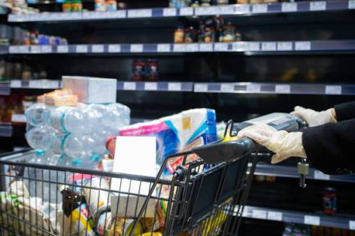 17 March 2020, Baden-Wuerttemberg, Göppingen: A supermarket customer pushes his full shopping trolley with hygienic gloves past an empty shelf. Because of the hamster purchases, many products are no longer available in the supermarket. Photo: Tom Weller/dpa (Photo by Tom Weller/picture alliance via Getty Images)