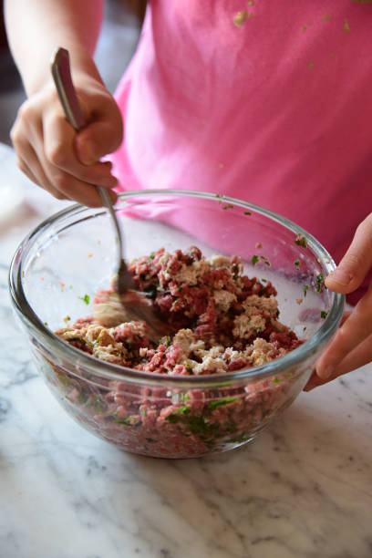 Mixing the ingredients to make meatballs in a glass bowl with a fork. One of the steps in the preparation of homemade beef meatballs in a domestic kitchen in Italy
